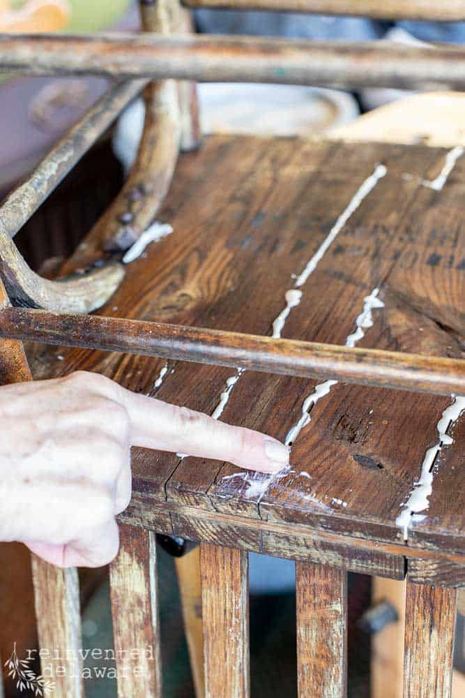 lady pressing glue into cracks of broken chair seat