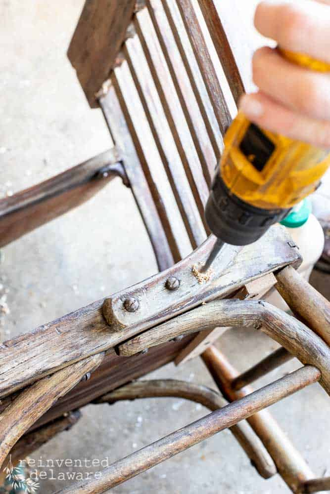 lady using power drill in broken chair bracket repair project on antique school desk chair