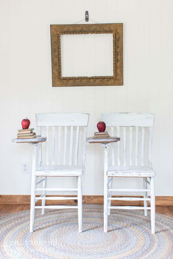 front view of matching antique desk chairs that have been painted and staged with stack of books, red apple and antique frame on wall