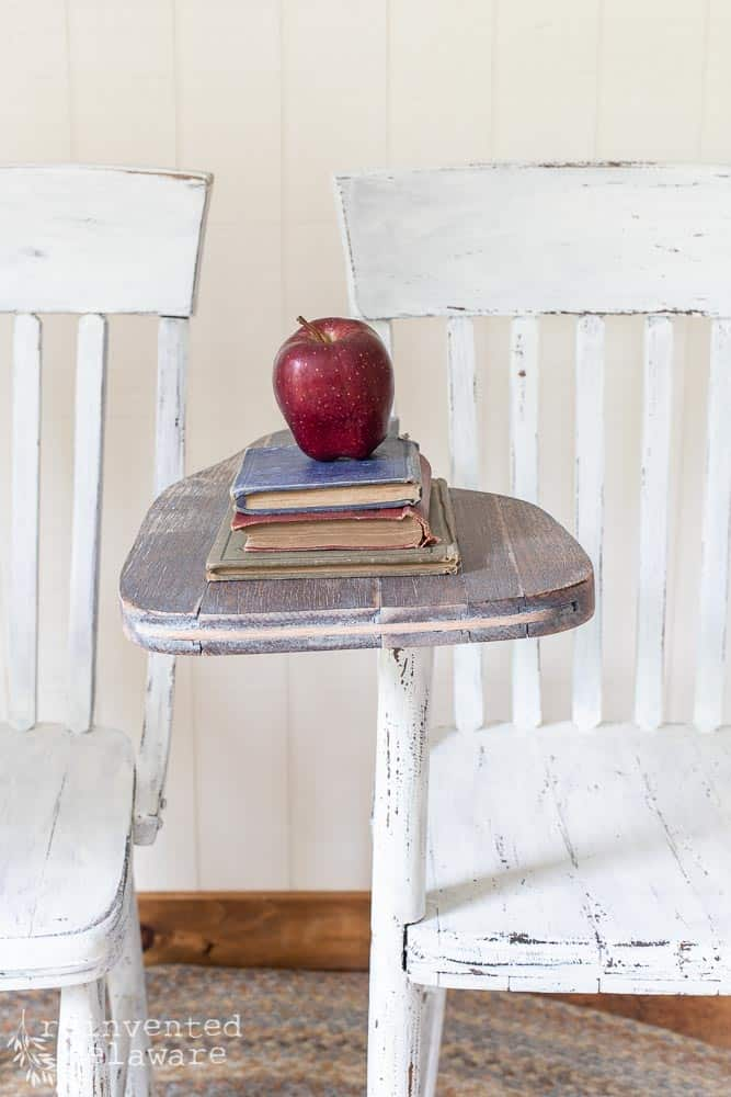 close up of desk area on vintage desk chair with stack of vintage books and red apple
