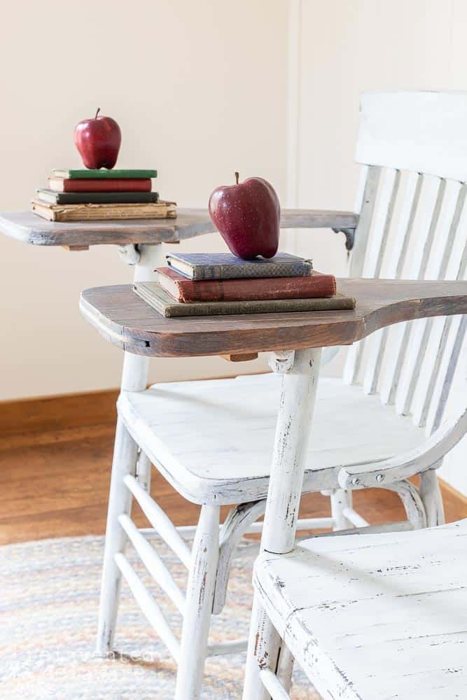 side view of pair of matching desk chairs that have been painted in farmhouse white milk paint and staged with vintage books and red apple