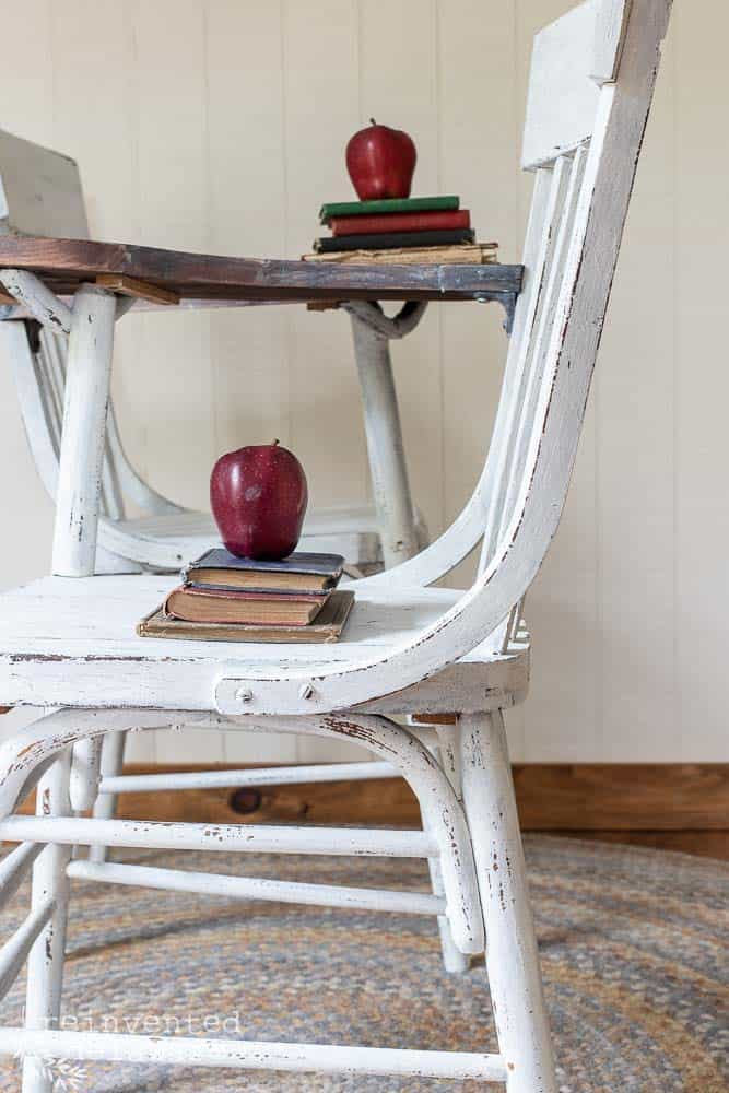 side view of antique desk chair highlighting chippy paint finish with red apple and vintage books