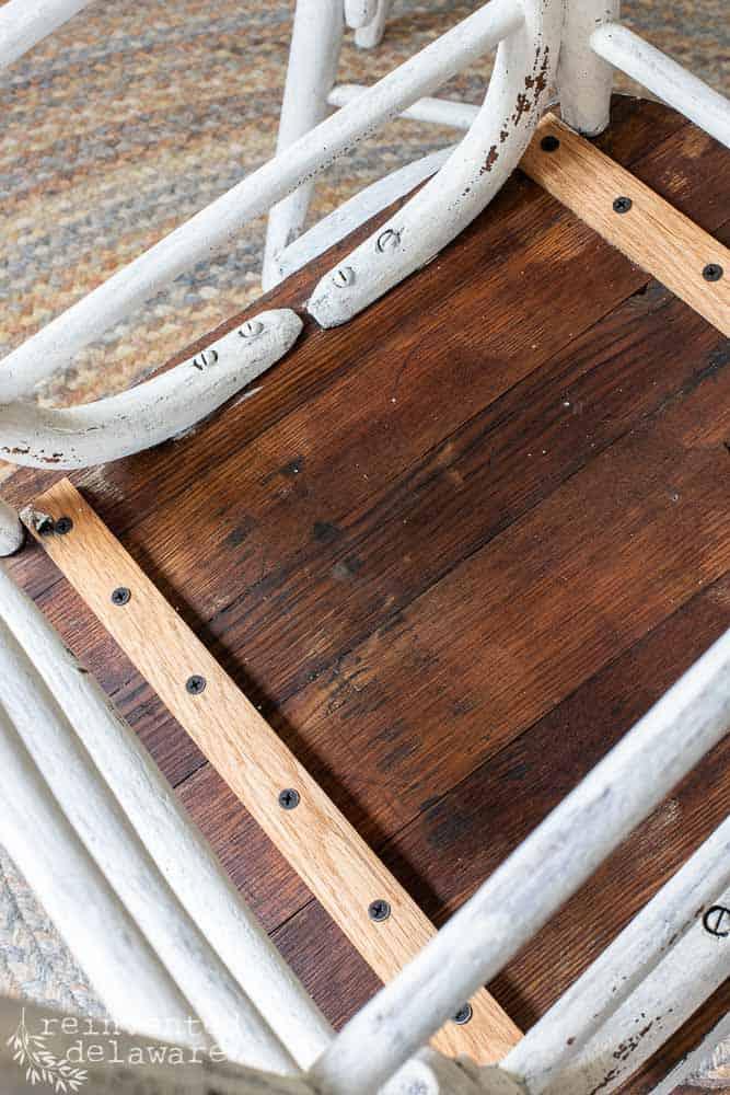 underside of desk chair showing easy chair seat repair using oak boards, glue and screws