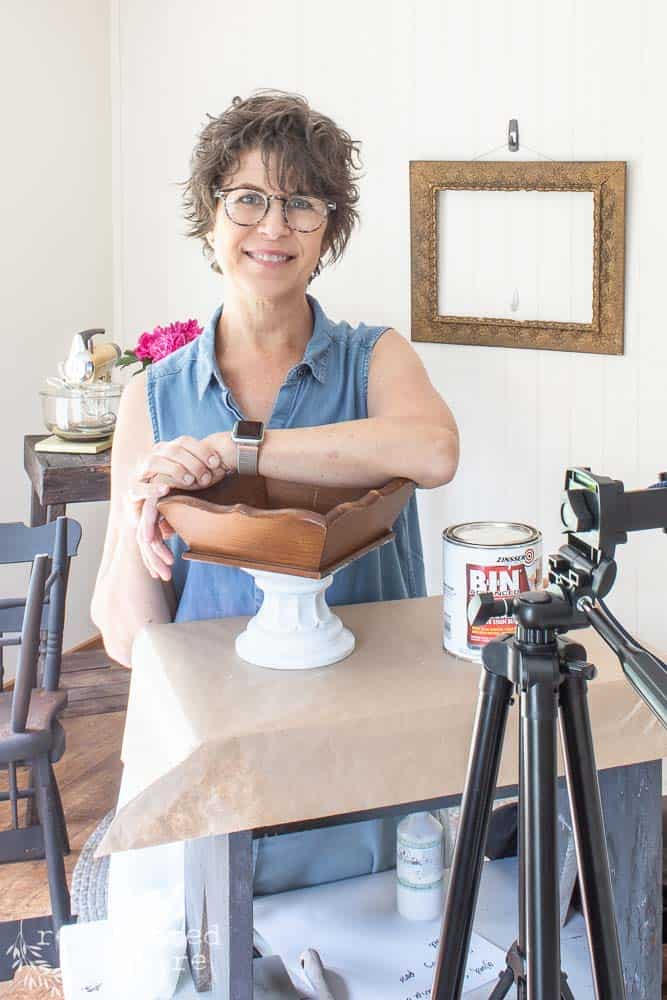 lady with her arm leaning on upcycled wooden tray makeover before the tray was painted with supplies and tripod ready for an Instagram Live Demo