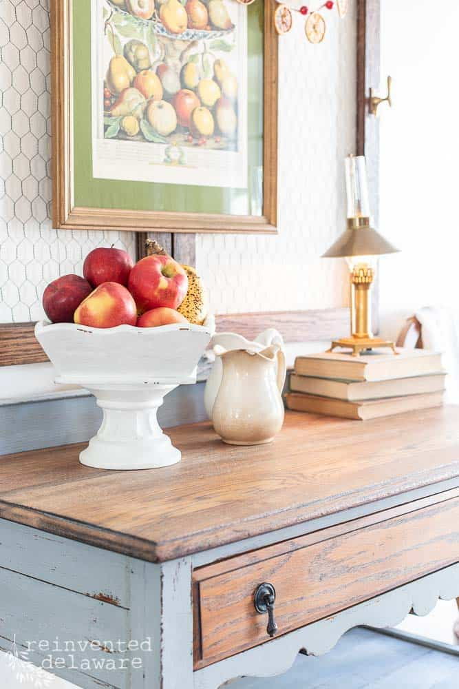 upcycled wooden tray after makeover staged on buffet with fresh apples and ripe bananas and other home decor items