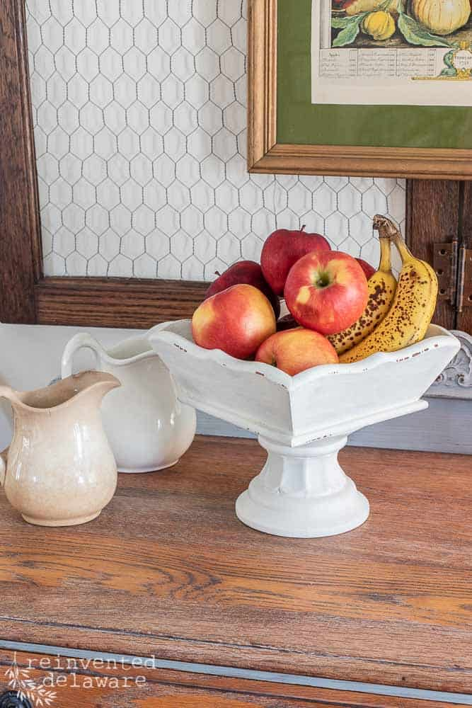 top view of upcycled wooden tray staged with apples and bananas in tray and two ironstone pitchers on the side