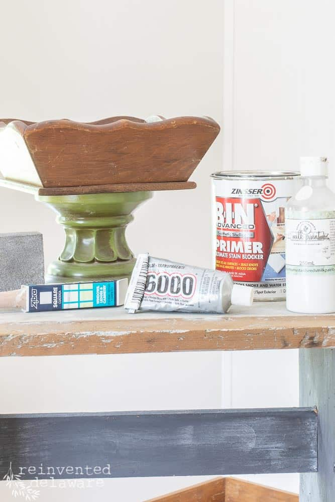 wood tray glued to green candle stand with supplies in foreground including Bin Shellac Primer, E6000 glue, Zibra Paintbrush, Miss Mustard Seed Bonding Agent, snading bock