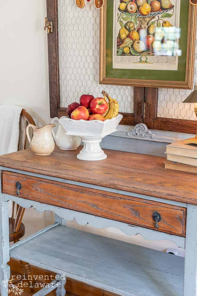 dining room buffet with upcycled wooden tray, ironstone pitchers, stack of books and wall art