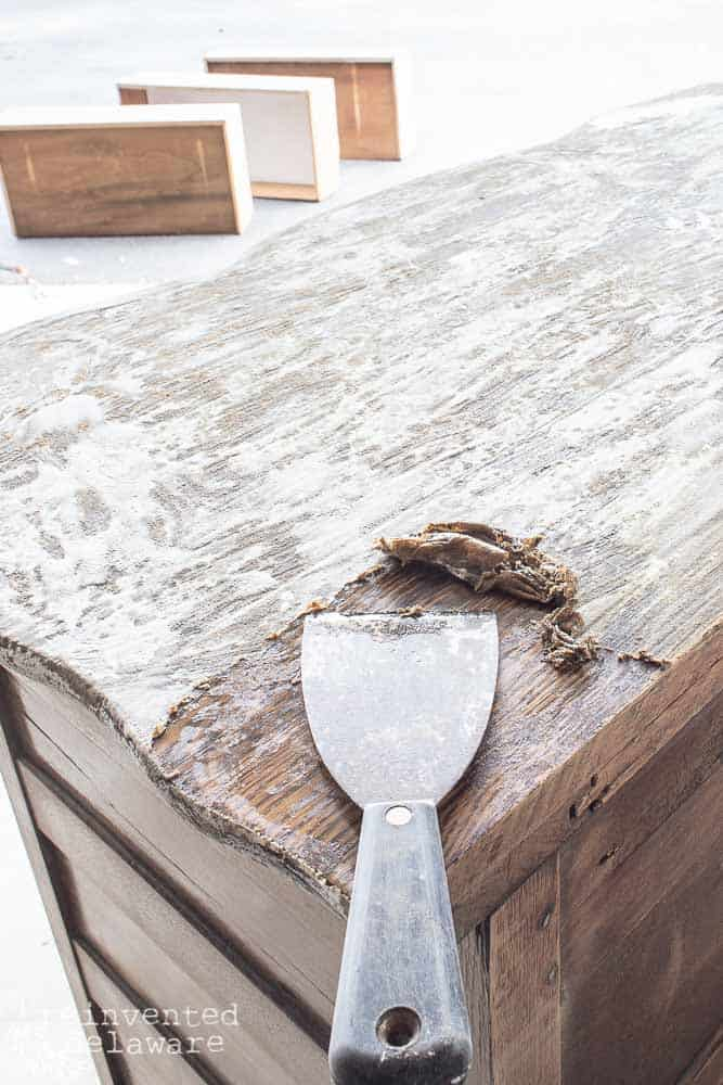 """old finish being scraped off of old dresser with a 3"""" putty knife"""