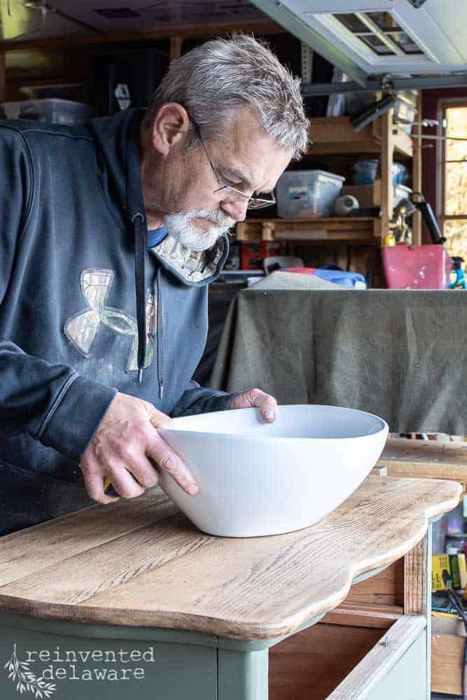 man measuring for vessel sink in the repurpsoed dresser converted to a bathroom vanity blog post