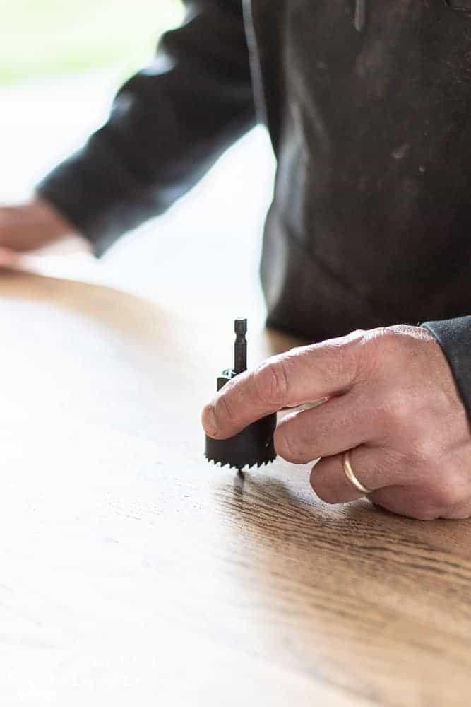 man showing large drill bit for oak dresser makeover