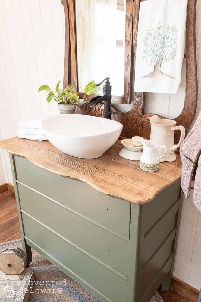 wide shot of top of dresser showing restored wood top staged with various bathroom vanity items