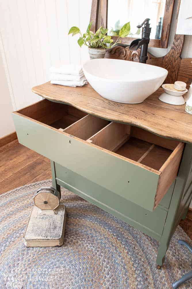top drawer of dresser outfitted for plumbing on dresser/vanity upcycle staged with sink, towels, soaps and a Pothos plant