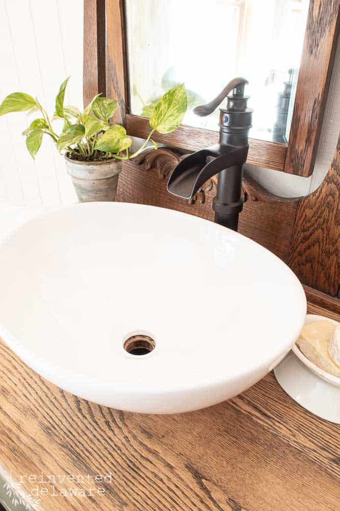 close up of vessel sink and old fashioned pump style faucet