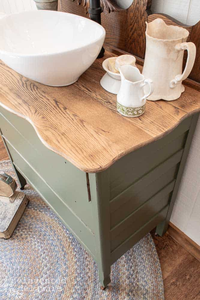 wide shot of restored wood top on dresser makeover staged with various vantiy items like soaps and a small water pitcher