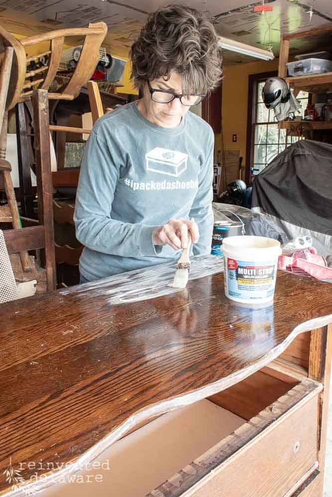 lady applying Multi Strip paint and finish remover with a chip brush on top of antique dresser