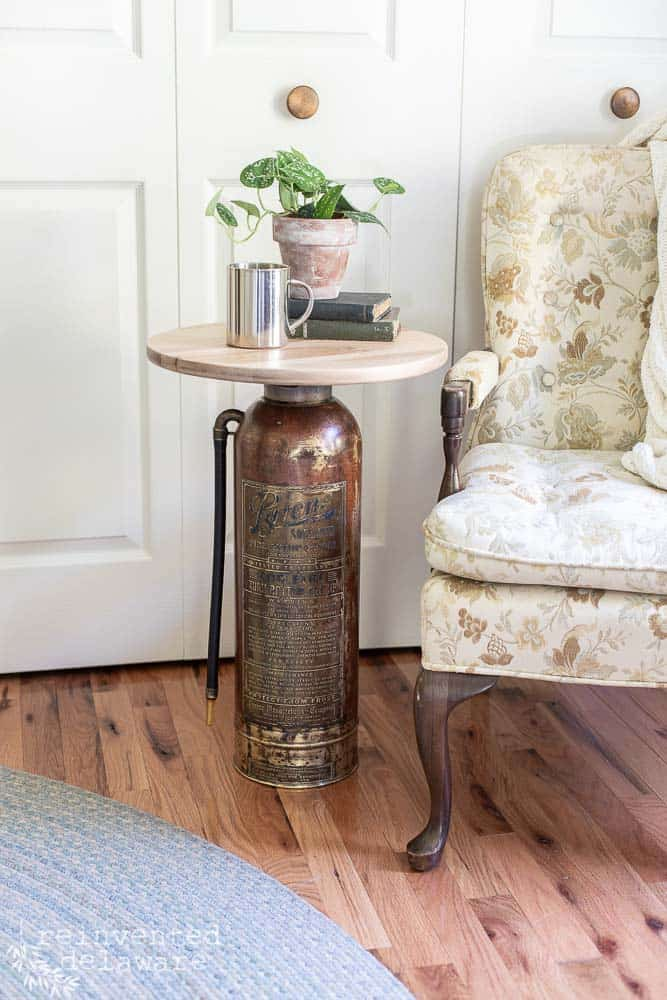 vintage fire extinguisher upcycled into a side table sitting next to a vintage chair