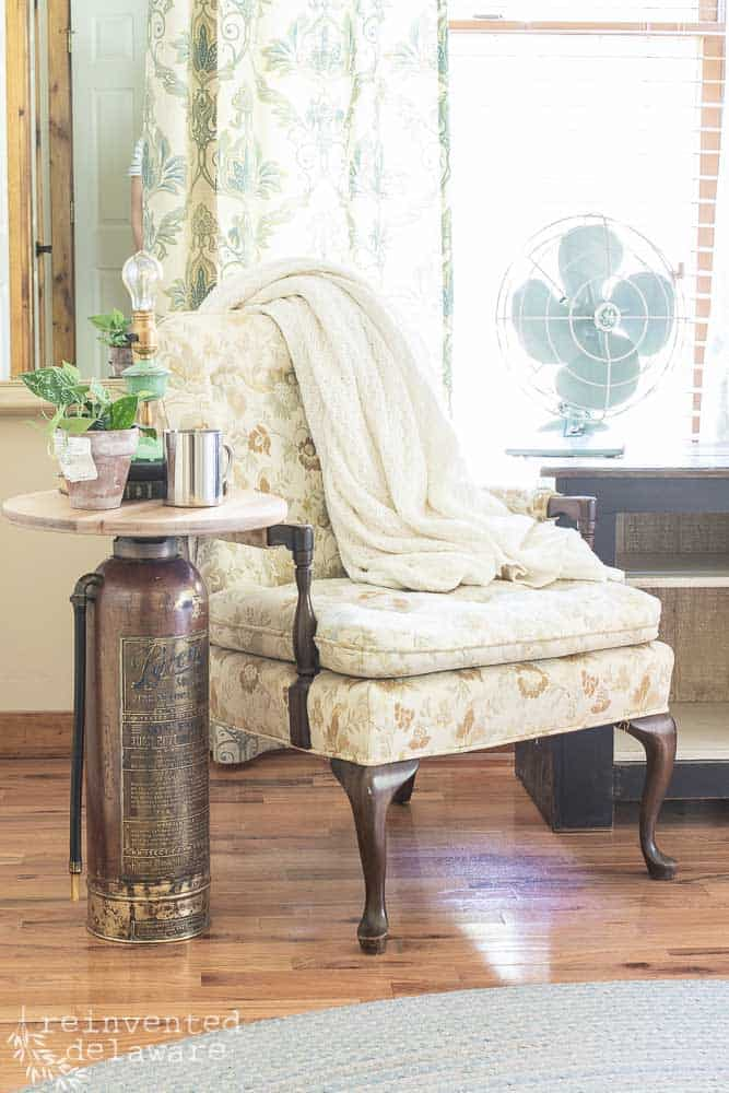 vintage upcycle fire extinguisher side table staged with various items on top and sitting next to a vintage side chair