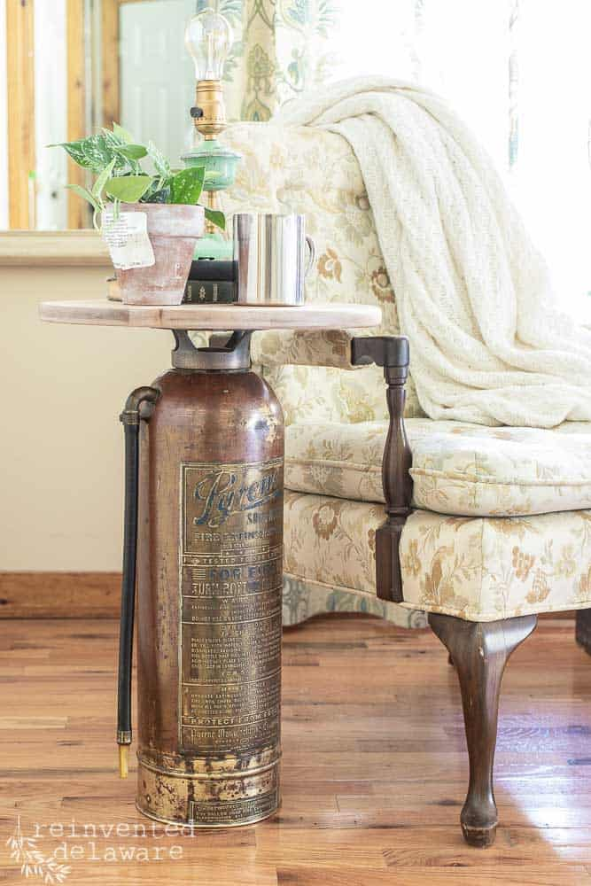 antique fire extinguisher side table staged with chair sitting next to it and various items sitting on top of side table