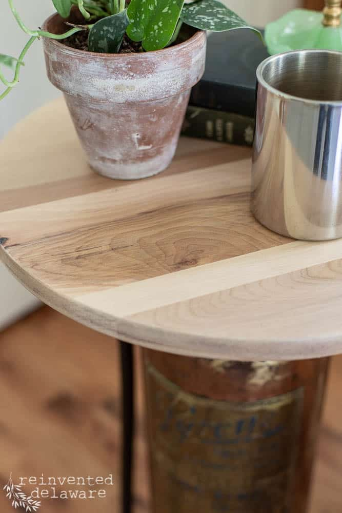 close-up of wood top made from a barstool and used as top of upcycled fire extinguisher converted to a side table