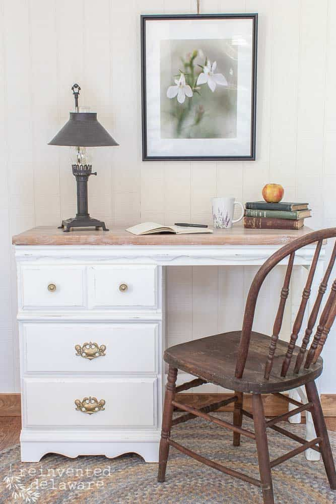 desk makeover idea showing painted base of desk with white waxed top and staged with lamp, books, chair and wall art
