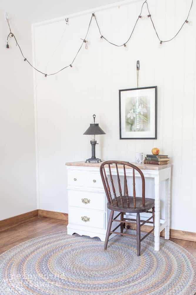 side view of desk showing makeover ideas and staged with chair, lamp, books, wall art and hanging lights