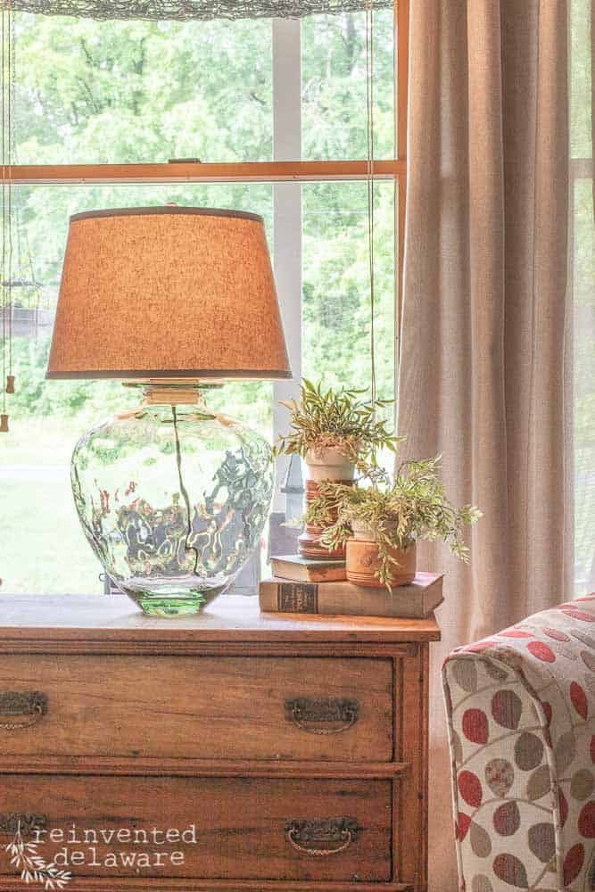 upcycled glass jar into a side table lamp sitting on top of vintage washstand with faux plants
