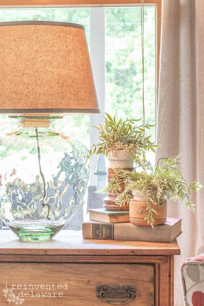 glass jar upcycled into lamp with light bulb turned on and faux greenery