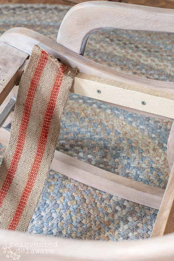 first strip of upholstery webbing being attached to new wood bracket on rocking chair