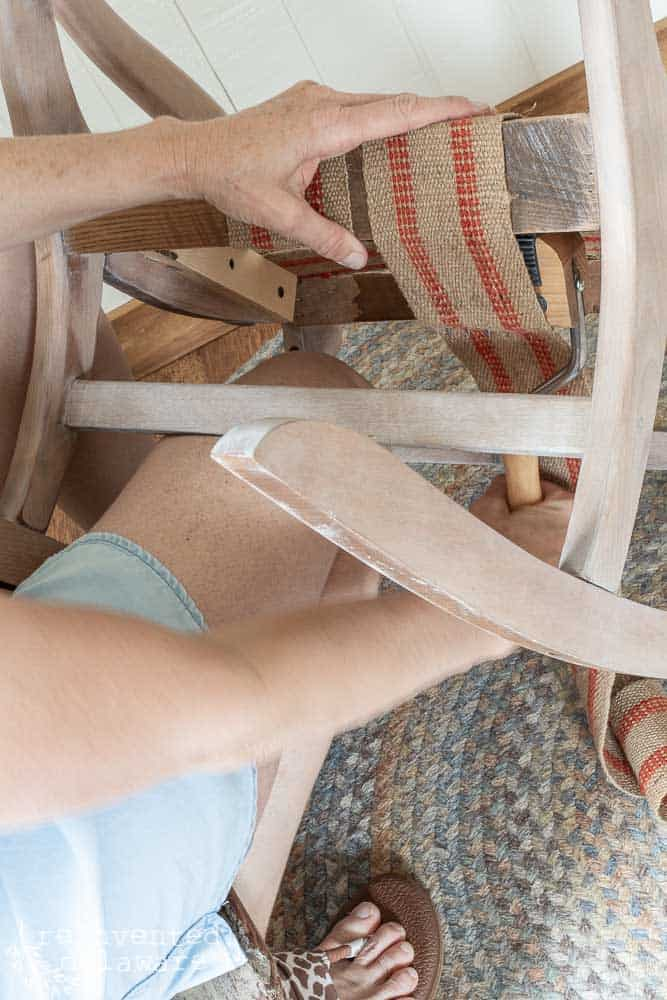 lady using upholstery webbing stretching on rocking chair upholstery project