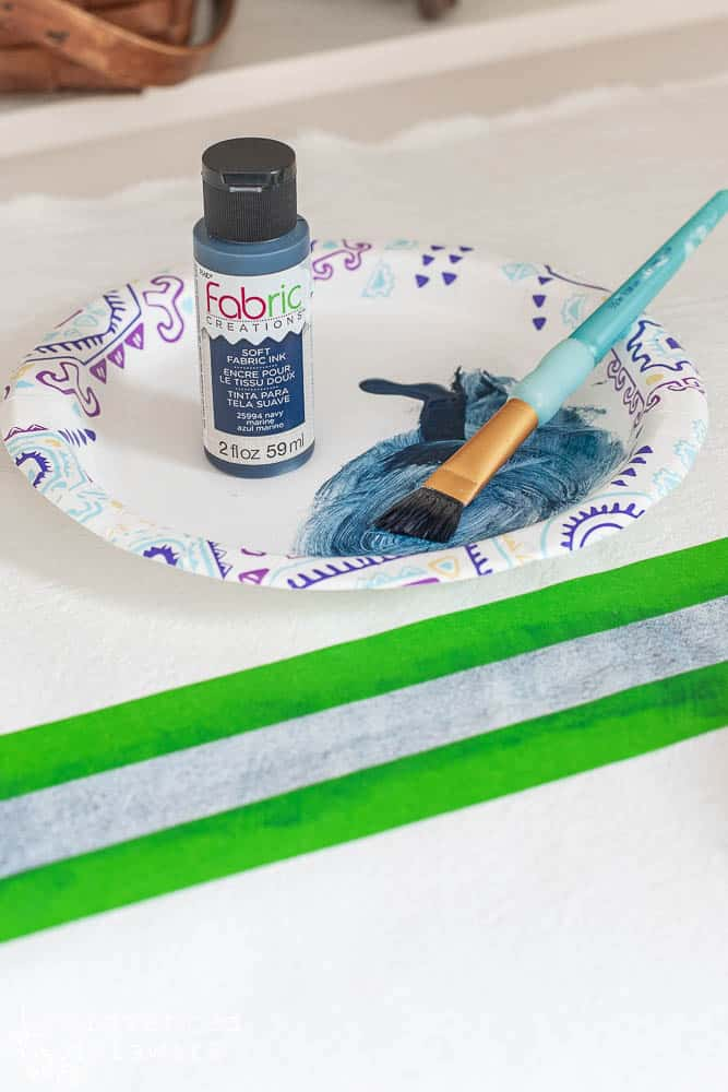 fabric paint, paper plate, paint brush and fabric taped of to paint grainsack style stripe