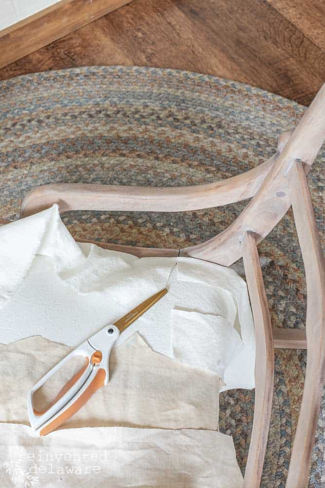 rocking chair with fabric and scissors laying on the seat of the chair