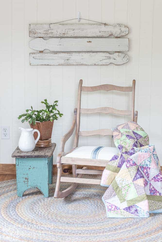 recovered rocking chair with quilt on side, small side table with plant and pitcher, wall art on wall