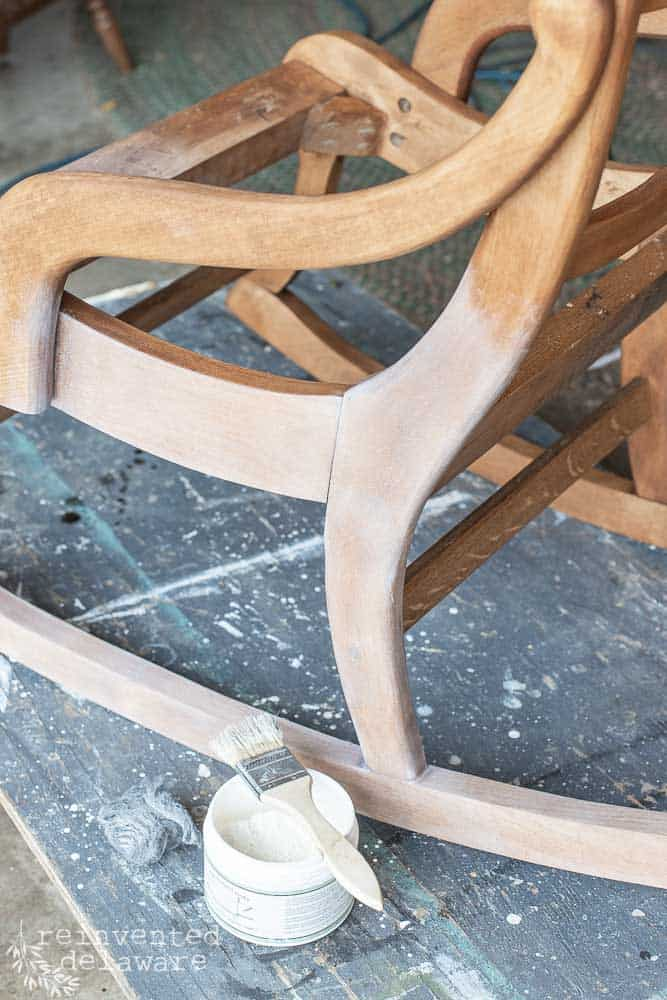 miss mustard seed white wax being applied to wood frame on rocking chair