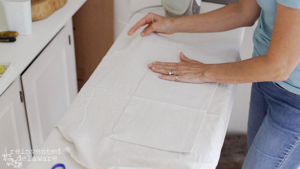 lady at ironing board prepping pocket for back wrap apron sewing tutorial