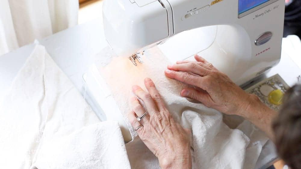 lady at sewing machine stitiching the understitching around neckline of wrap apron
