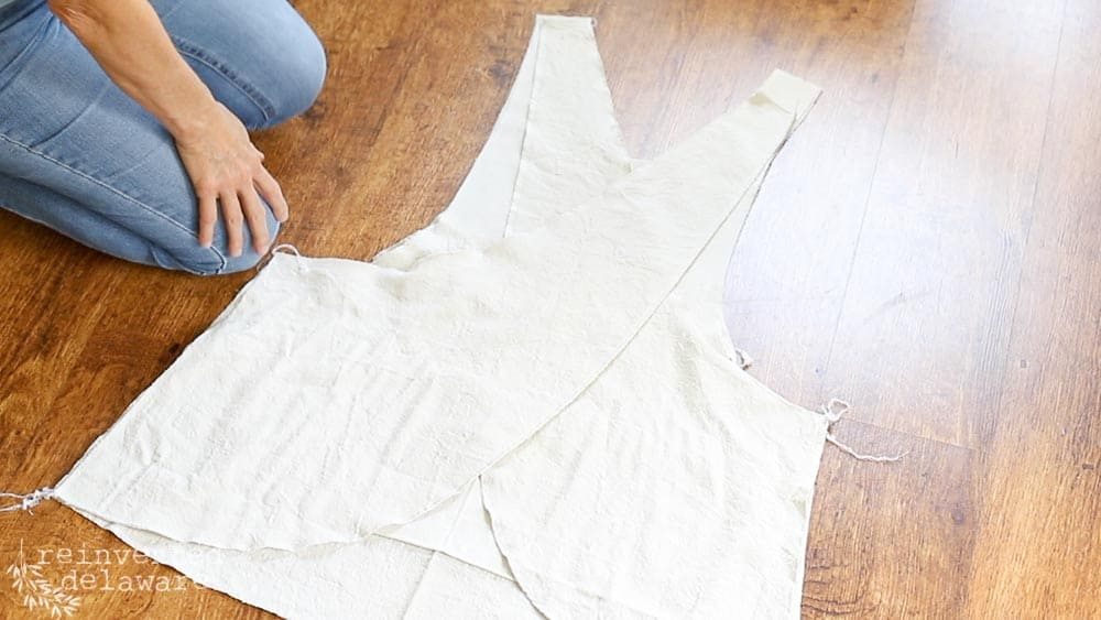 lady showing how to lay out fabric pieces for how to sew an apron blog post and youtube video