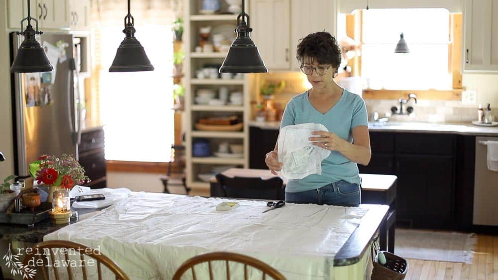 lady laying out pattern pieces on fabric for how to sew an apron tutorial