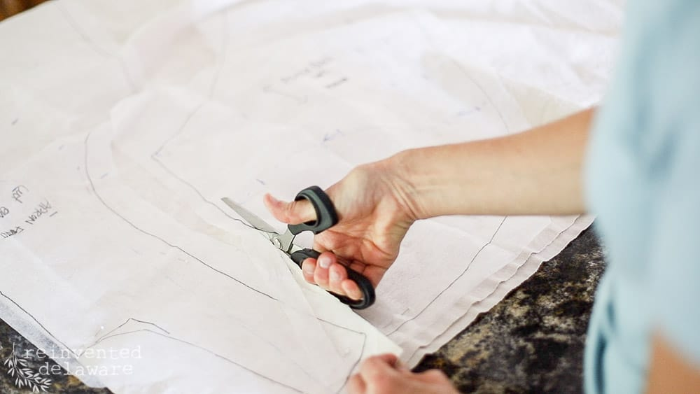 lady using scissors to cut out fabric for how to sew an apron tutorial blog post and youtube video