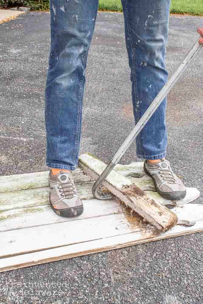 lady using crow bar to remove railings on picket fence sections