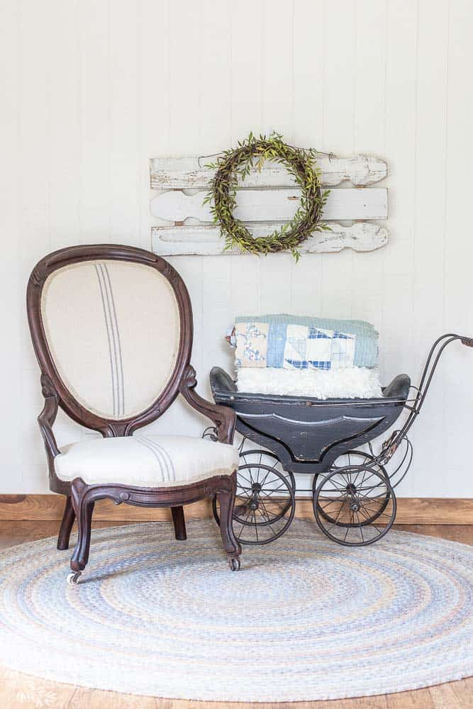 staged shot of restored and reupholstered antique chair with vintage stroller and wall art