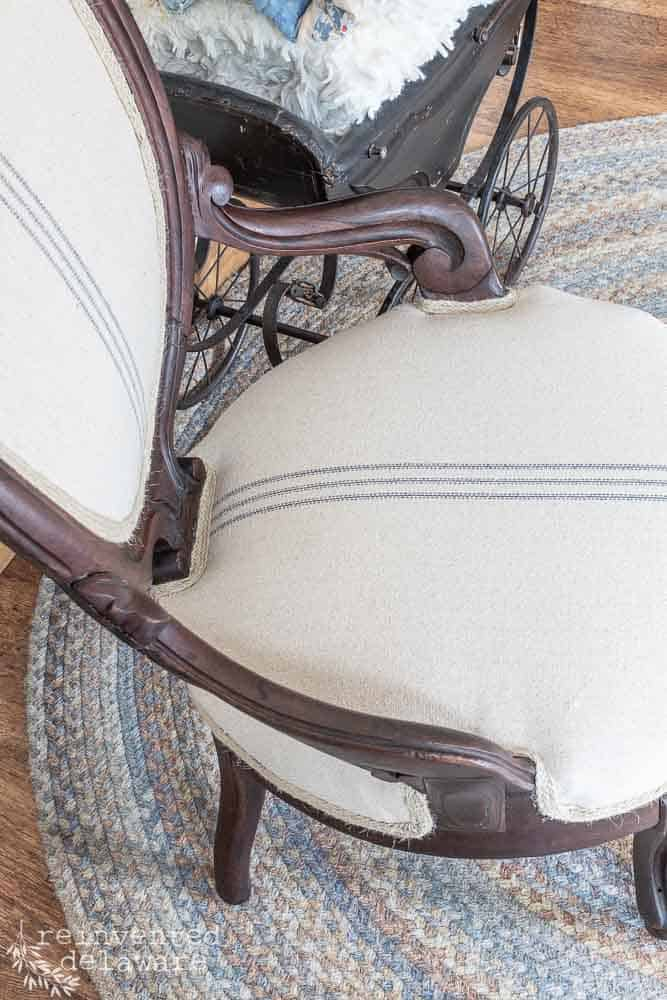 close up of seat on chair that has been reupholstered with grainsack style fabric in a blue stripe