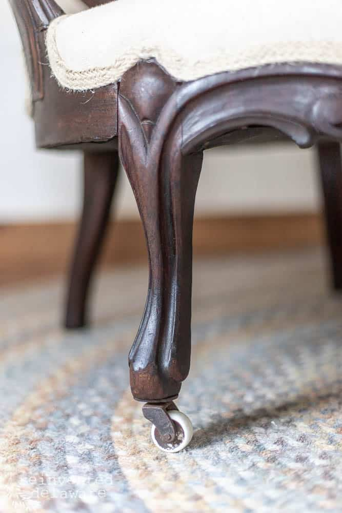 close up of caster on furniture makeover project called how to recover a chair