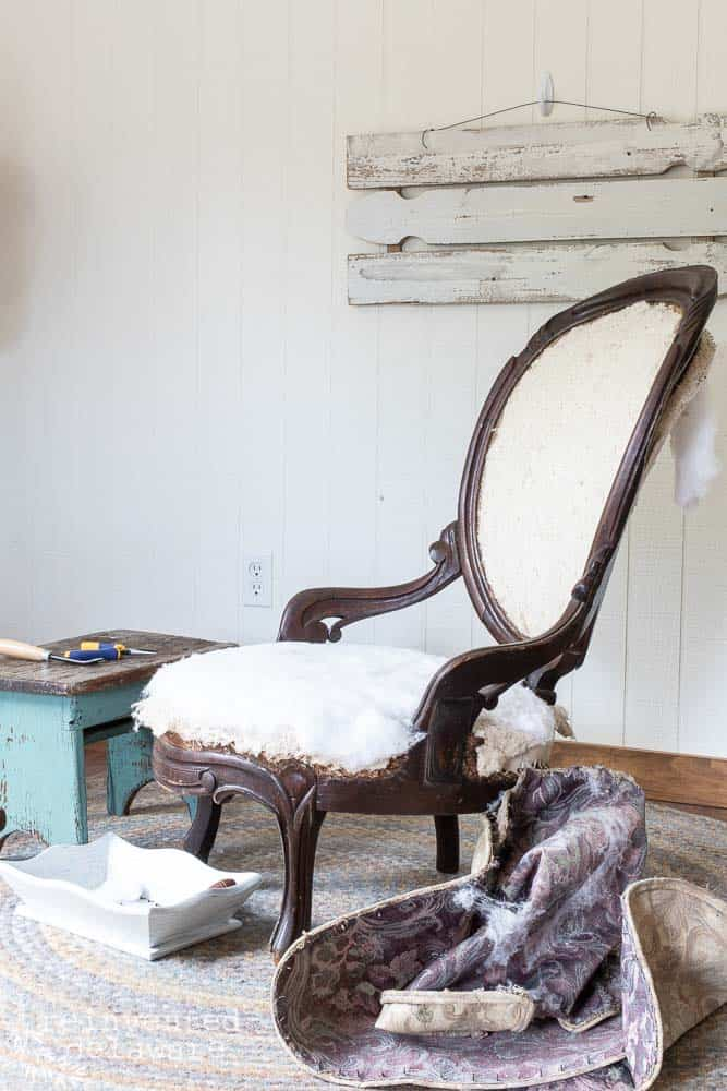 antique victorian chair after old fabric has been removed and ready for reupholstery