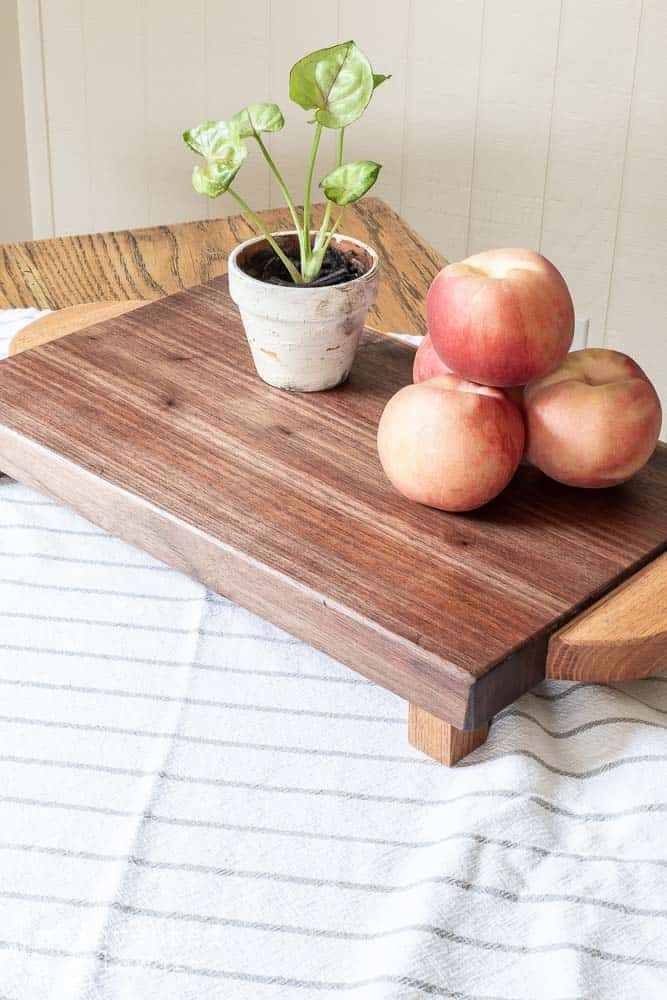 top view of waxed wood chopping board with peaches and a plant on top