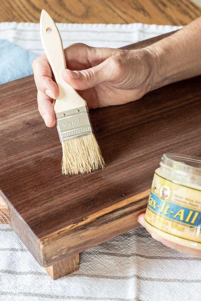 lady applying wax on wood cutting board