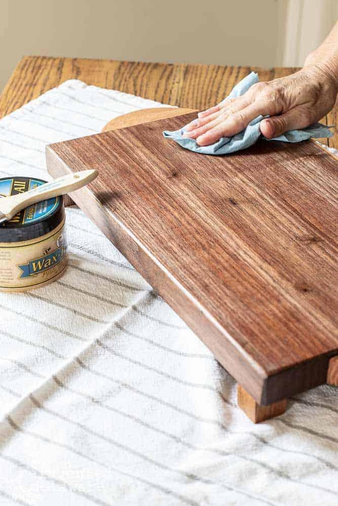 lady buffing wax on wood cutting board