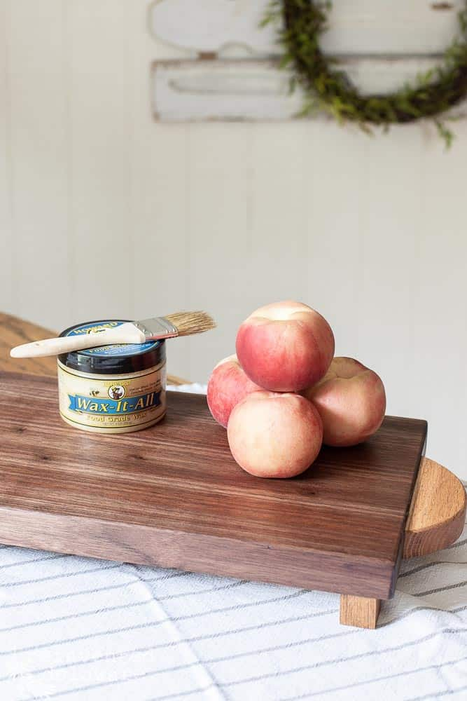 stack of peaches and green plant on top of waxed wood cutting board