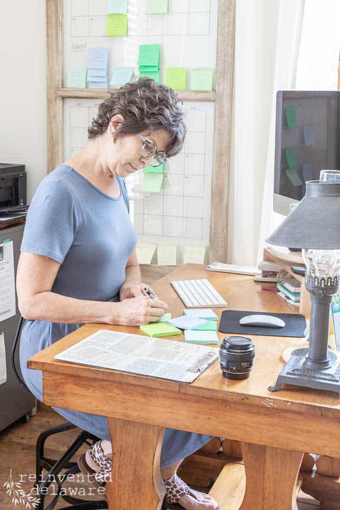 lady sitting at desk working on creating an editorial calendar