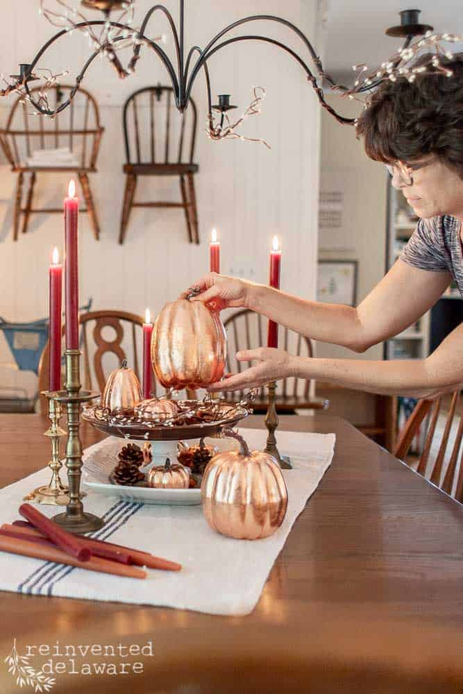 lady placing a copper leaf pumpkin on a dining table for fall decoration